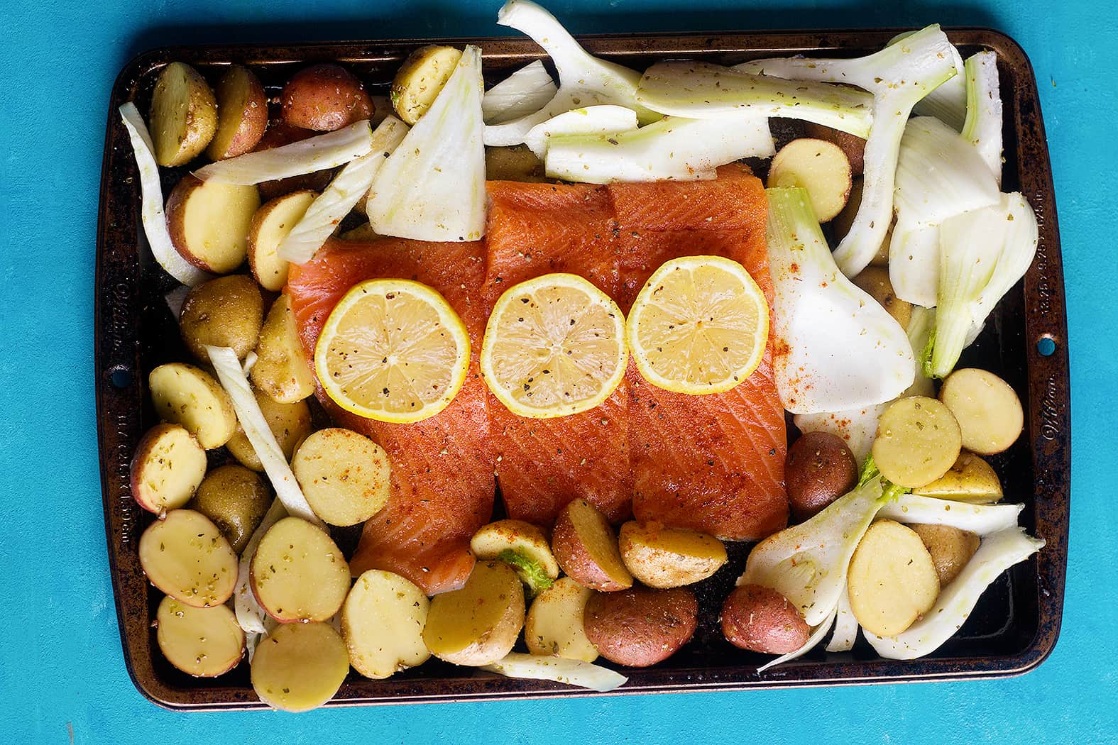 To make baked salmon fillet, mix all the spices with lemon and olive oil and brush them on salmon fillet. Spread the veggies around and bake.