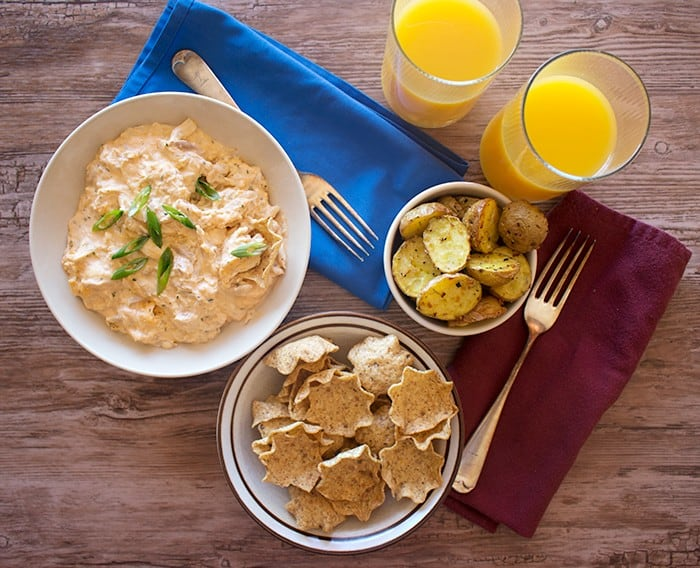 a bowl of buffalo chicken dip with tortilla chips, potatoes and two glasses of orange juice.