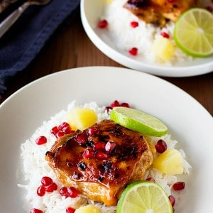 Chicken thighs baked in sweet and savory marinade and is served on white rice to make a complete meal! Pomegranate Pineapple chicken is perfect for parties or just a weekend meal!