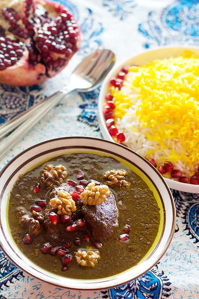 Top Fesenjoon with walnuts and pomegranate arils. Serve with saffron rice.