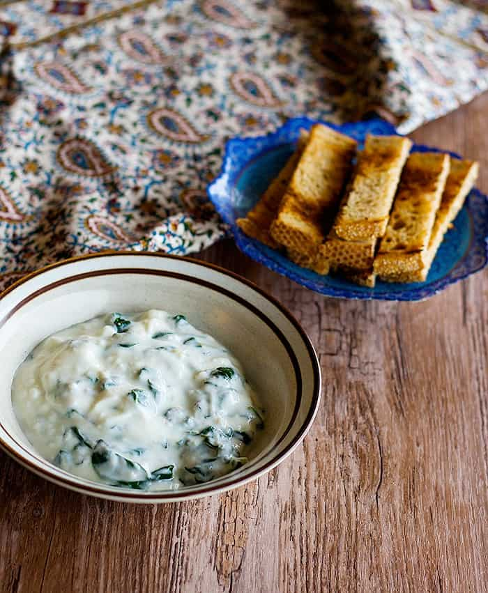 A bowl of spinach yogurt dip served with bread sticks.