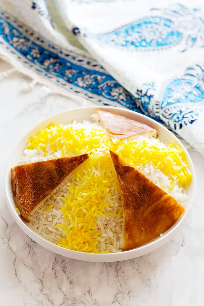 Persian Rice is the key element of Persian cuisine. Learn the easiest method with details once and make perfect Persian rice with a crispy golden crust called Tahdig every time.