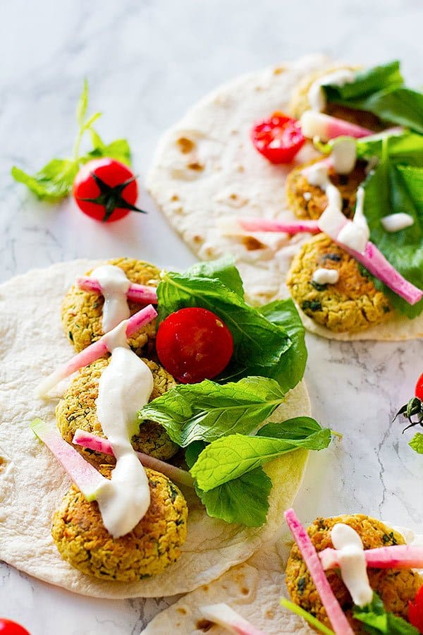 Baked falafels make a filling, healthy meal. Serve them with an easy tahini yogurt sauce and enjoy every bite of this delicious wrap!