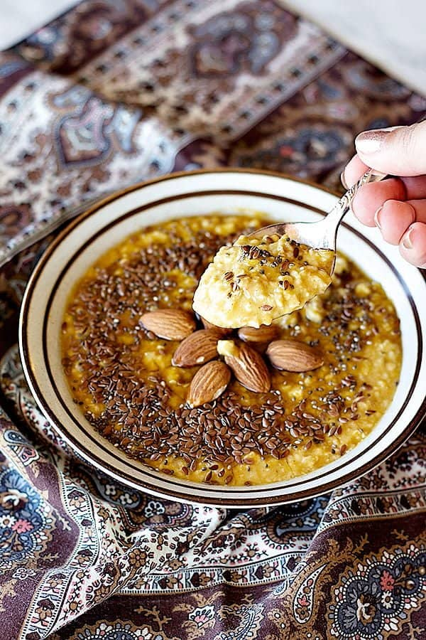 Easy pumpkin spice oatmeal topped with chia seeds and flax seed with whole almonds.
