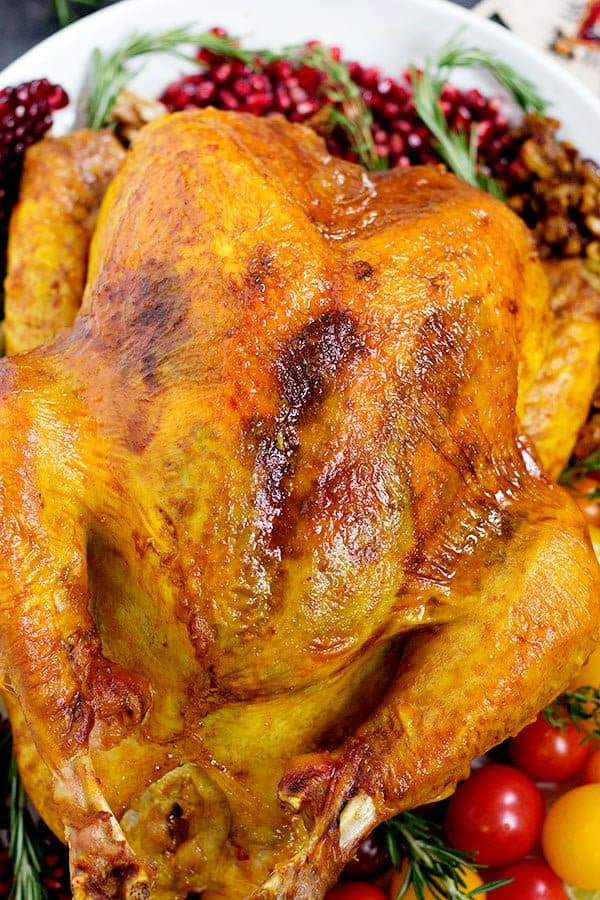 Delicious juicy roasted turkey recipe with spices and herbs that's perfect for Thanksgiving.