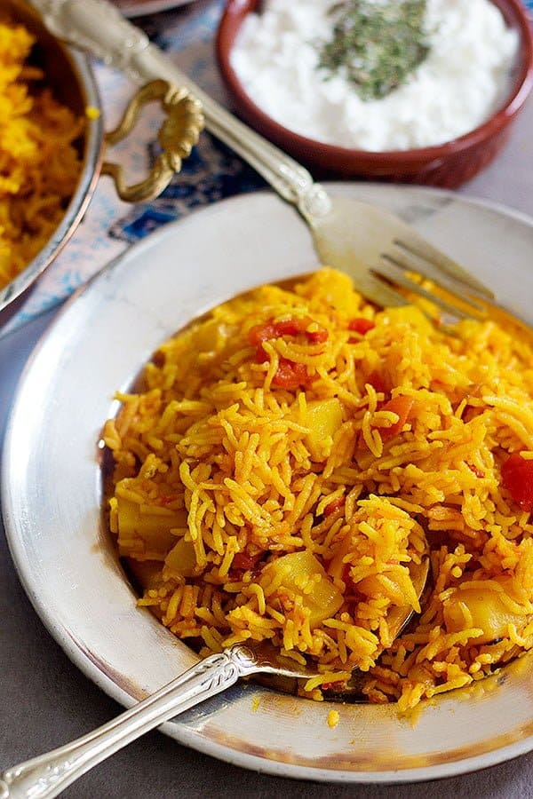 A plate of Persian style tomato rice with yogurt on the side.