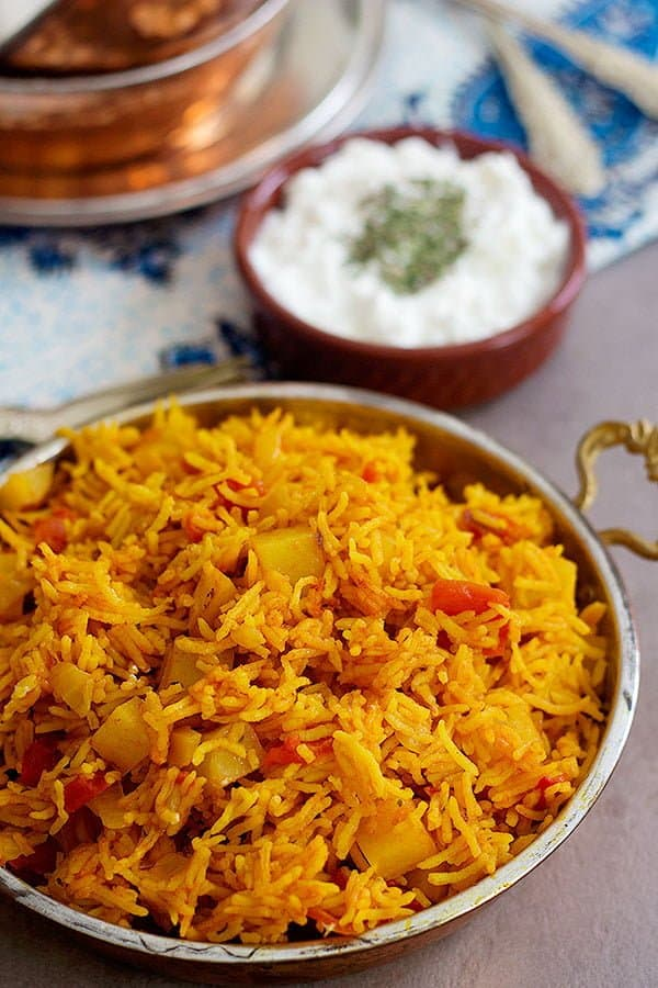 Tomato rice made Persian style and served with salad shirazi and yogurt topped with dried mint.