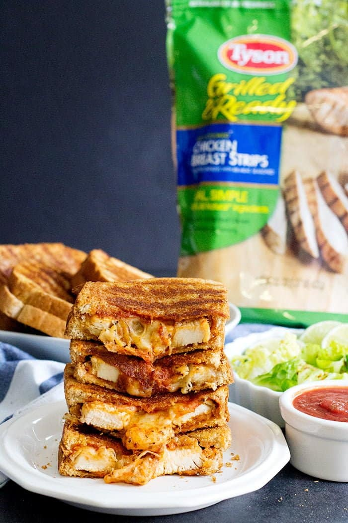 A stack of grilled cheese chicken parmesan sandwich with melted cheese.