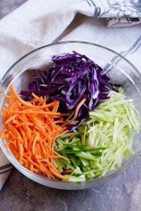Asian slaw made of shredded white and purple cabbage, shredded carrots and cucumbers. Mix all together in a large bowl.