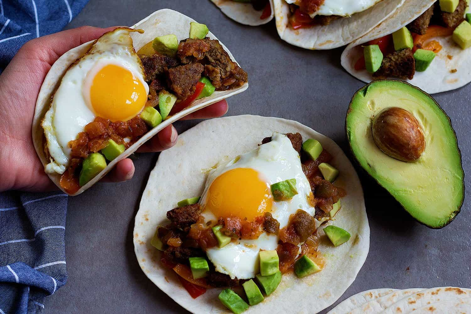 Breakfast Tacos Recipe - Tortillas filled with vegetarian sausage, avocados, onions, peppers and topped with a delicious sunny side up egg.