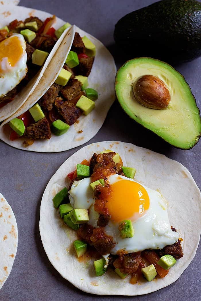 Breakfast Tacos Recipe - Top the tacos with sunny side up eggs, salsa and avocados.