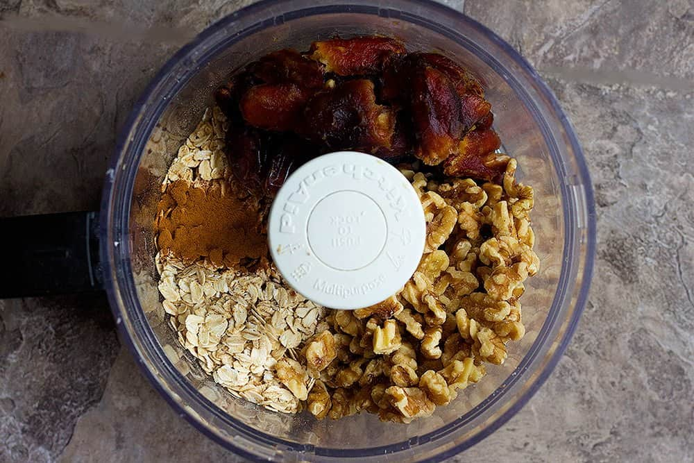 For this healthy granola bar recipe you need dates, walnuts, oats and cinnamon. Place all the ingredients in a food processor.