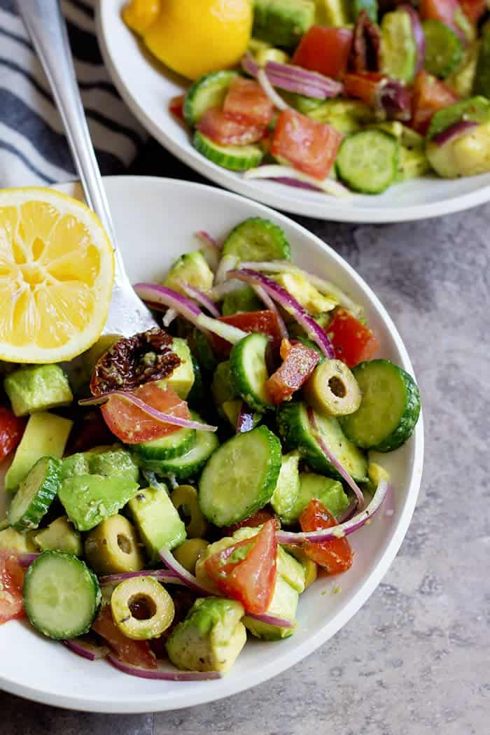 Serve avocado tomato salad in two smaller bowls with lemon.