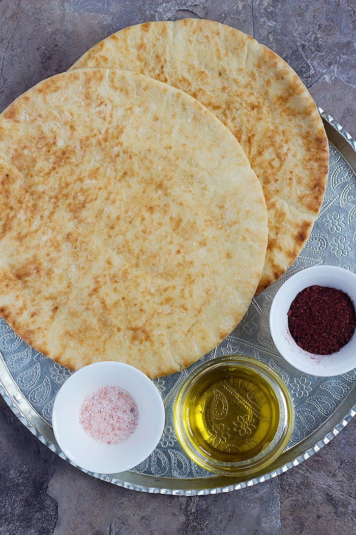 To make homemade pita chips you need pita bread, sumac, salt and olive oil.