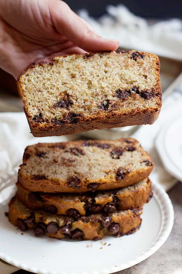 A slice of moist chocolate chip banana bread on top of a stack of moist chocolate chip banana bread slices