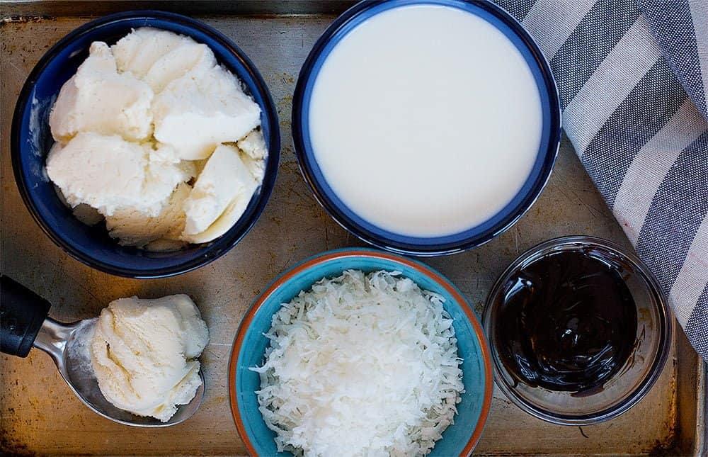 Coconut milkshake ingredients are vanilla ice cream, coconut milk, chocolate sauce and shredded coconut.