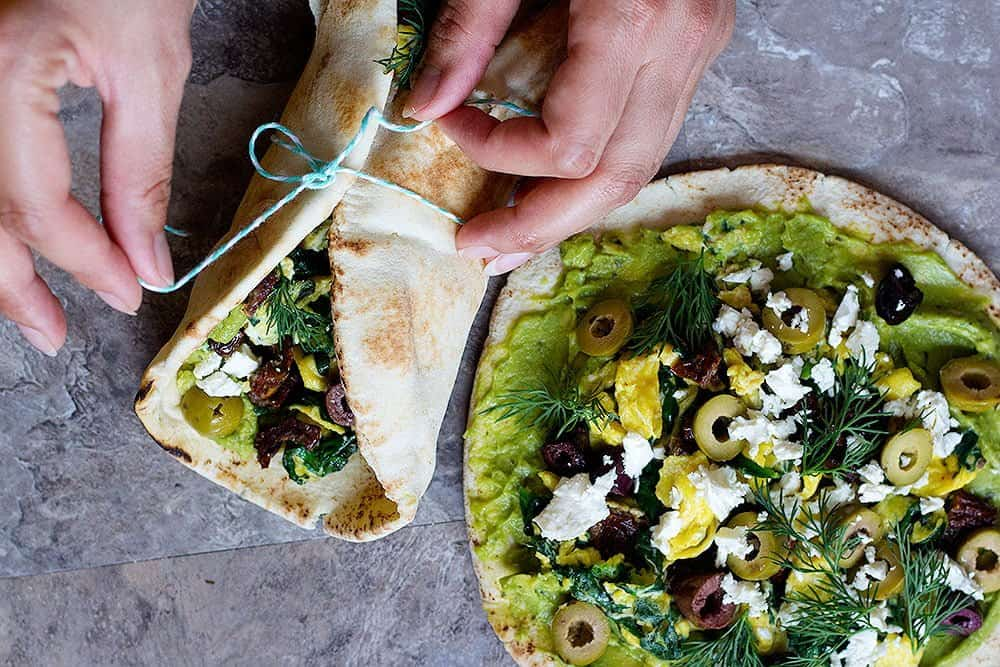 to make egg and avocado sandwich, spread avocado on pita and top with eggs, spinach, tomatoes, olives and feta cheese.