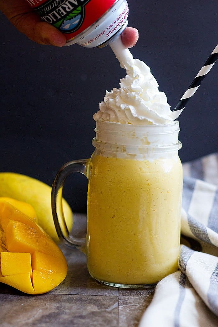 mango milkshake with ice cream is topped with whipped cream