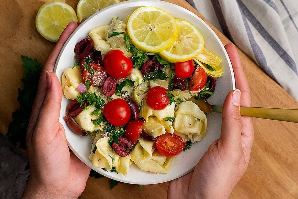 This greek tortellini salad is delicious and easy to make. It looks beautiful in a bowl served with lemons on the side.