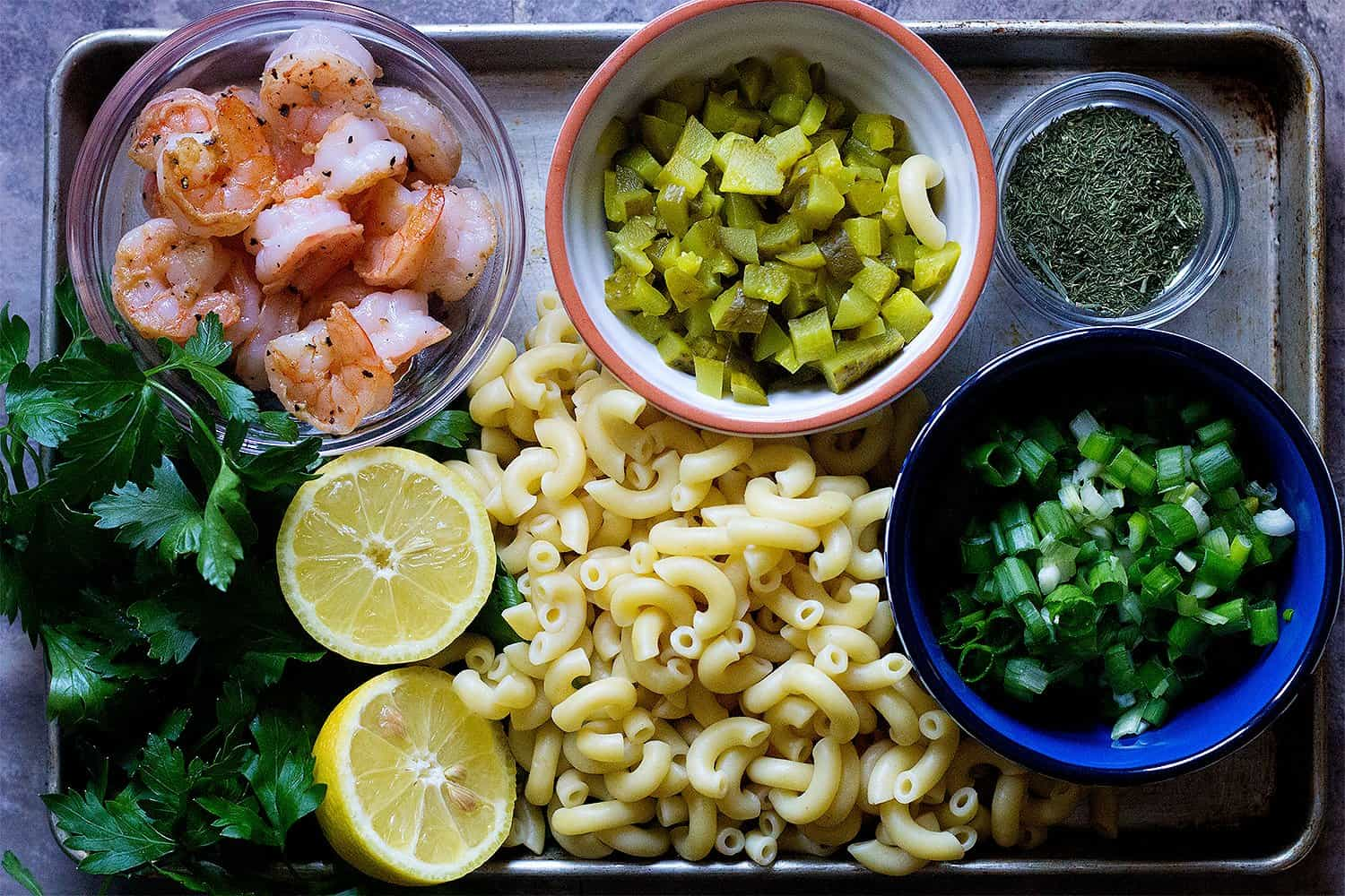 shrimp macaroni salad ingredients are cooked shrimp, pasta, parsley, dill, dill pickles, green onion, and lemon.