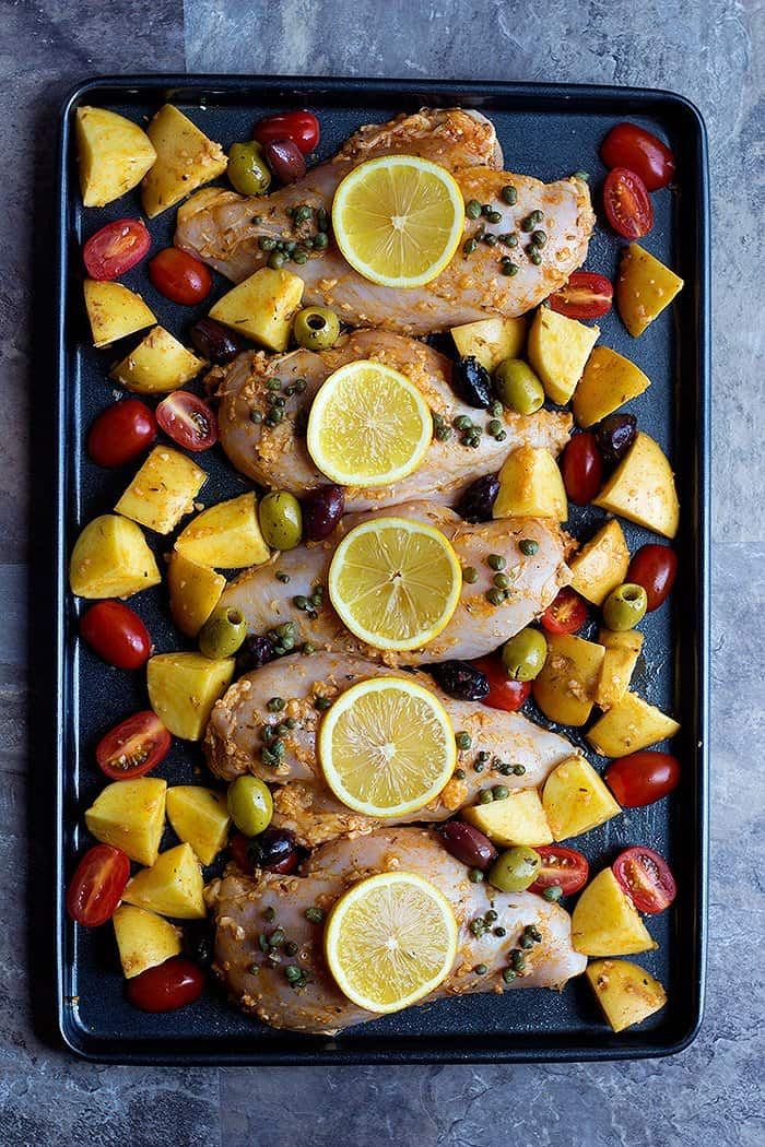 Mediterranean chicken marinade is made with lemon, olive oil, garlic and spices. Marinade the chicken and place it with the vegetables on a baking sheet.