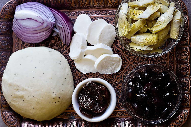 Mediterranean pizza ingredients are pizza dough, red onion, artichokes, kalamata olives, sun dried tomatoes and mozzarella