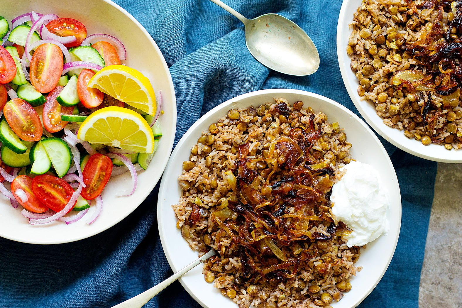Two bowl of Lebanese lentil rice topped with caramelized onion and served with a simple salad.
