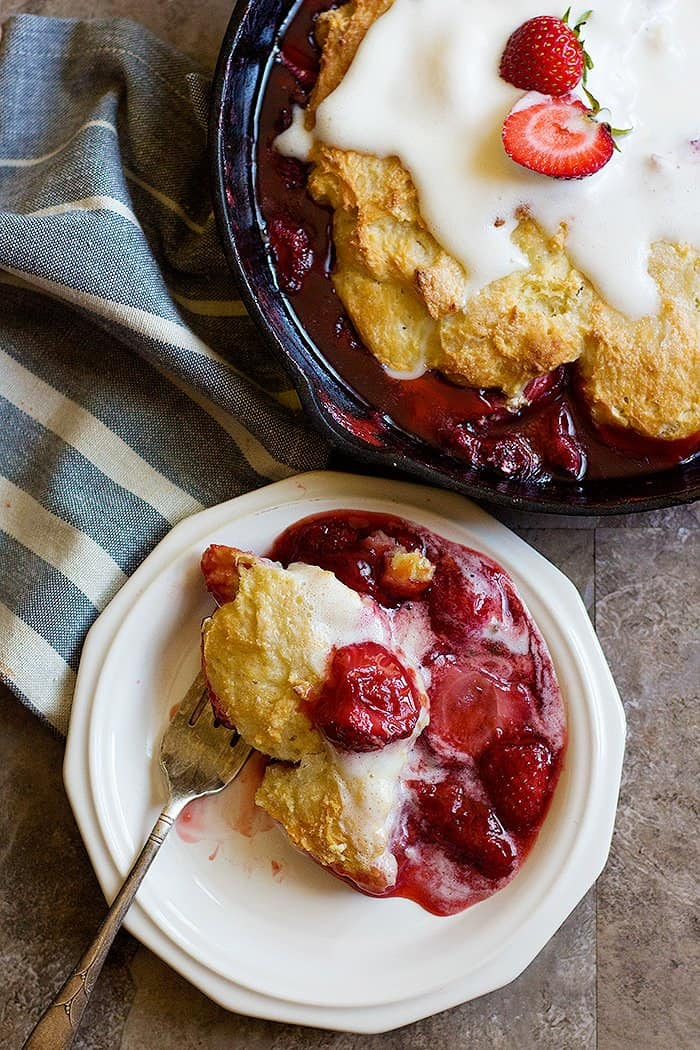 This strawberry cobbler recipe is easy to follow and has a thick filling and is topped with vanilla ice cream.