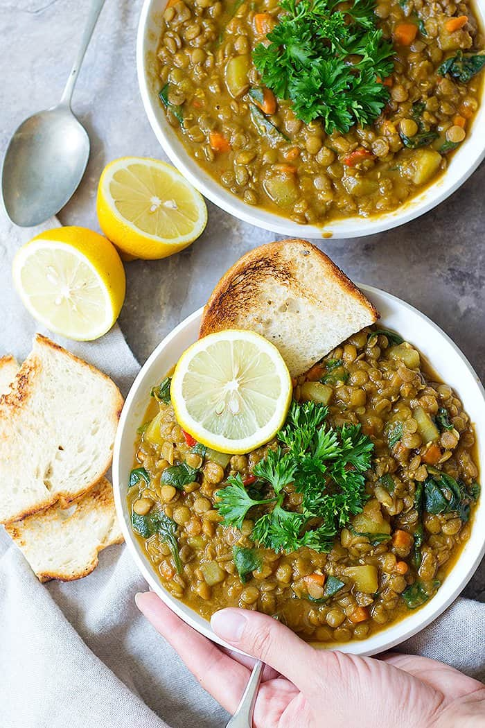 Two bowl of soup on a grey backdrop. Served with some toasted bread and lemon and topped with parsley.