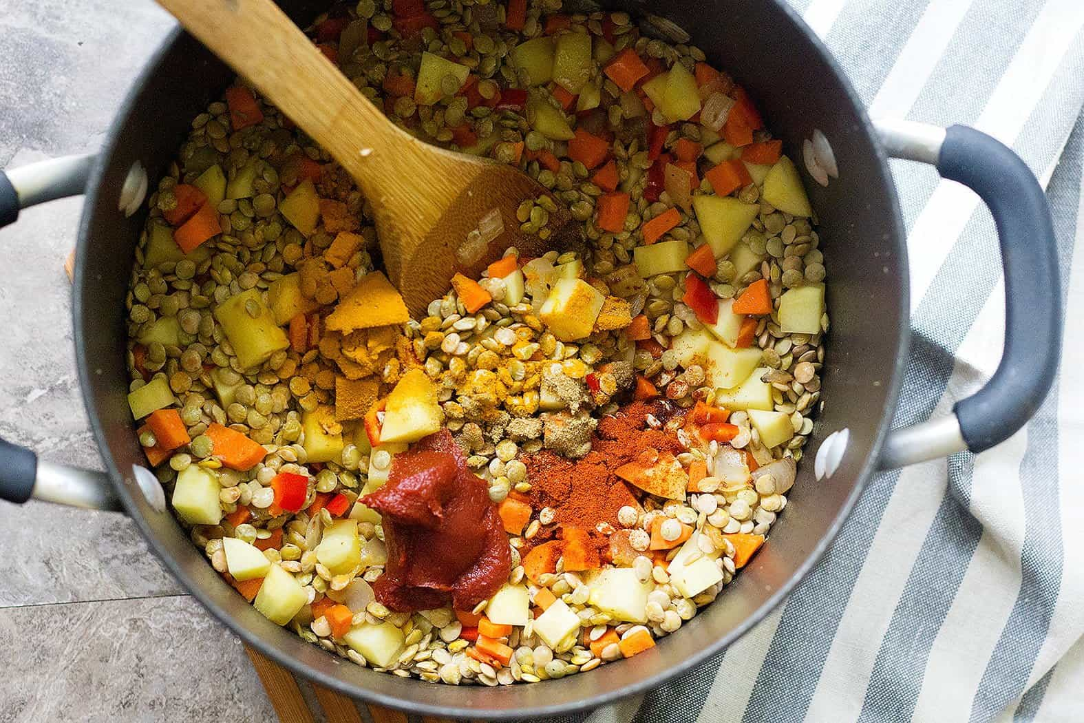 to make this simple vegetarian green lentil and spinach soup recipe saute onion and garlic, then add lentils, carrots, peppers and potatoes with spices.