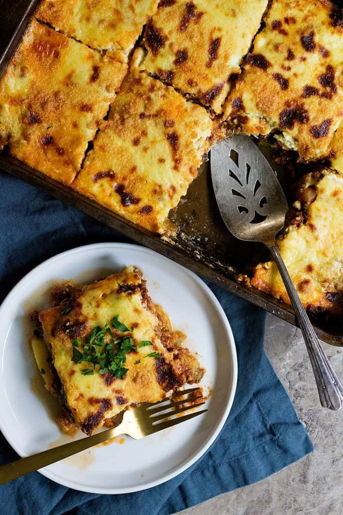 a slice of Greek eggplant moussaka on a plate and the rest in the pan.