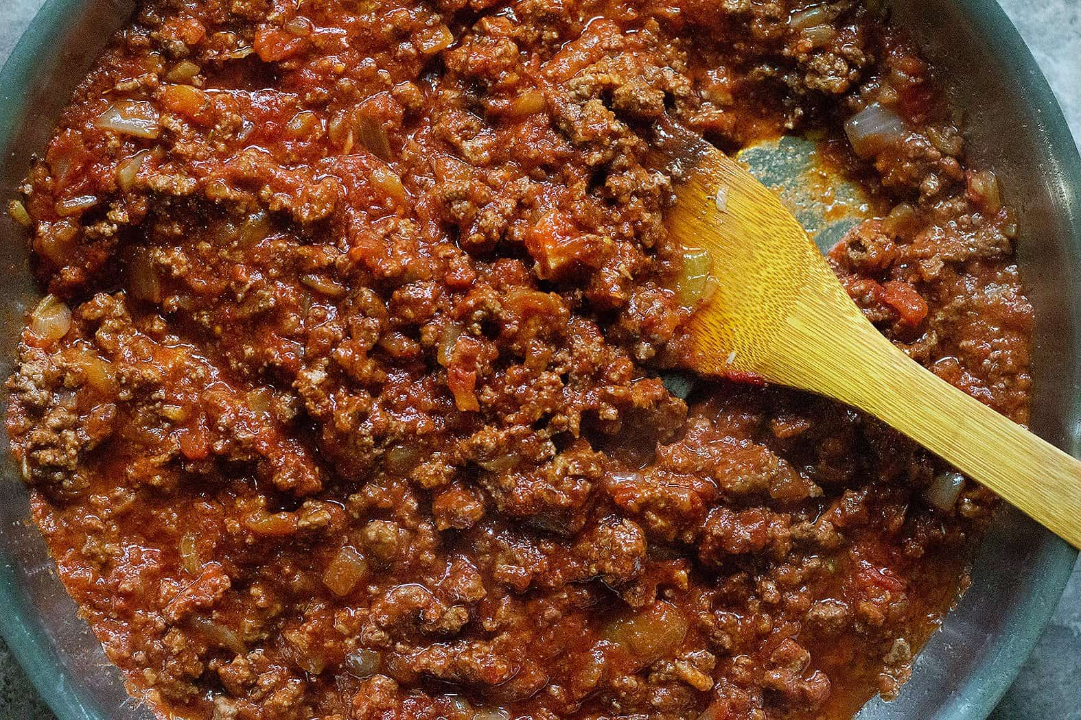 Add tomato paste and crushed tomatoes.