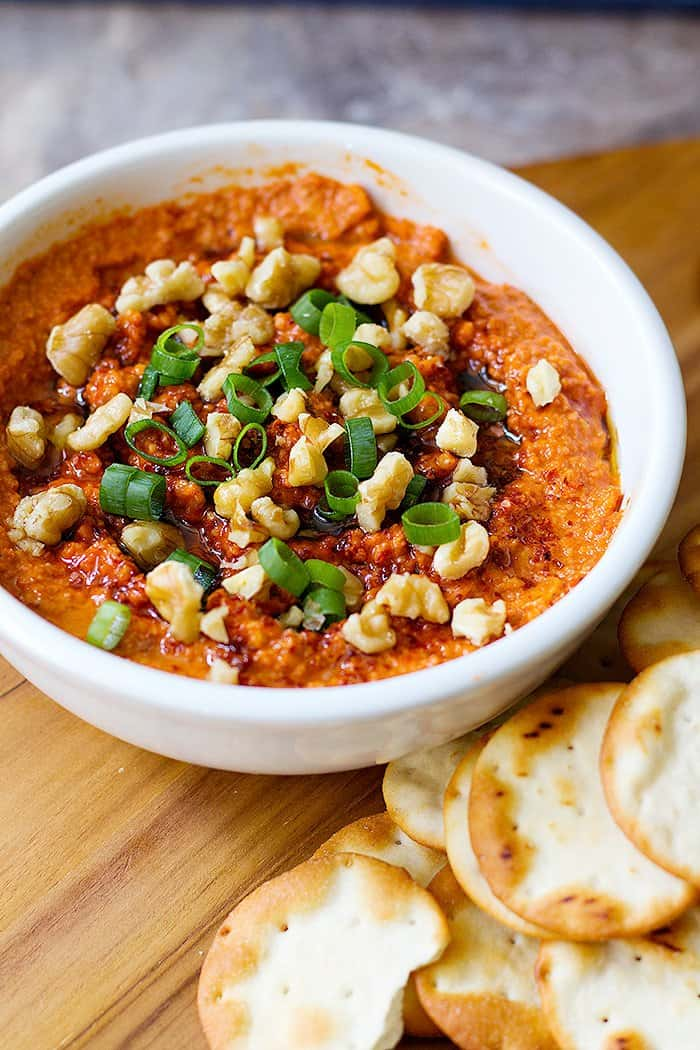 Roasted red pepper dip topped with walnuts and green onion.