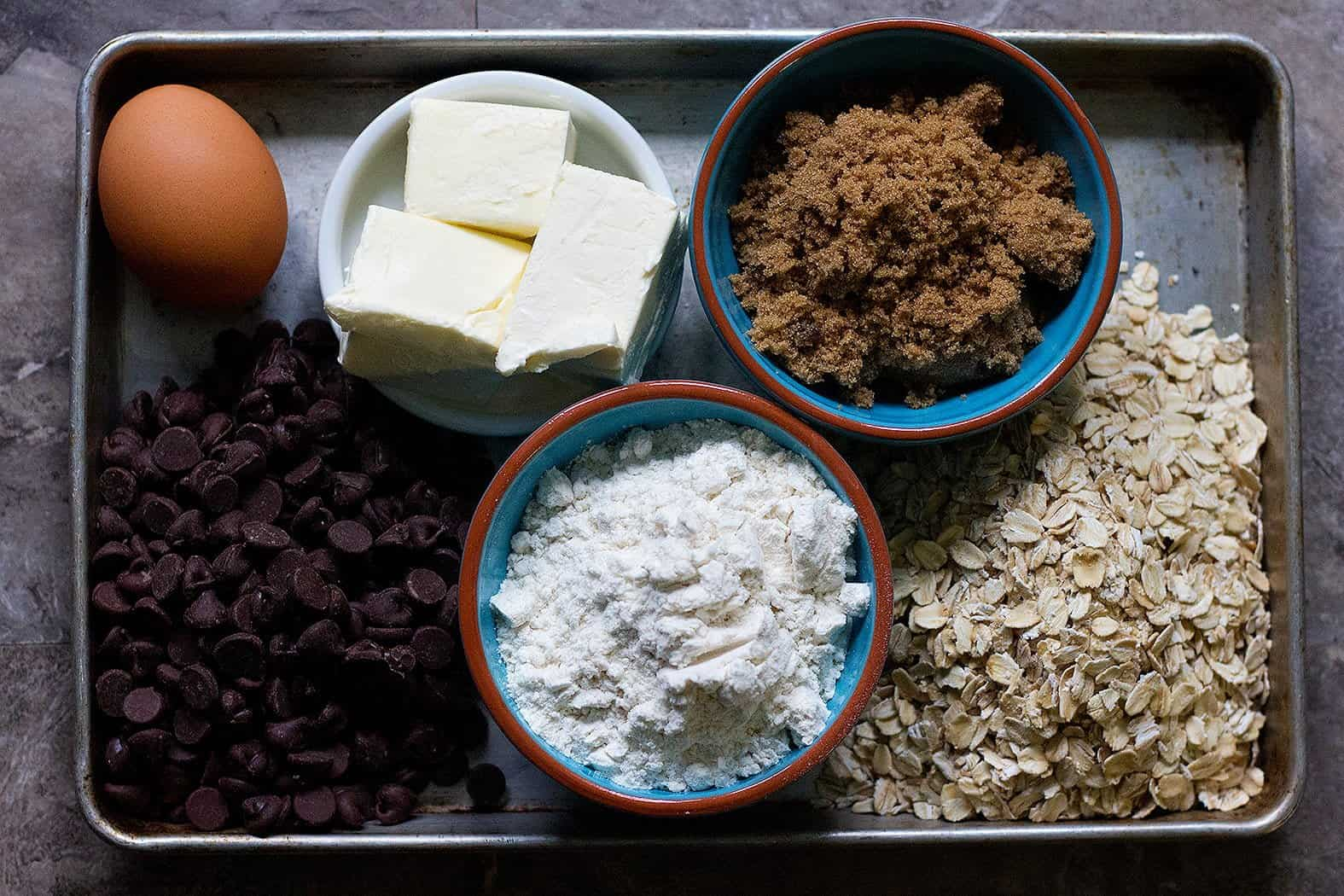 To make chewy oatmeal chocolate chip cookies you need eggs, butter, brown sugar, oatmeal, chocolate chips and flour.