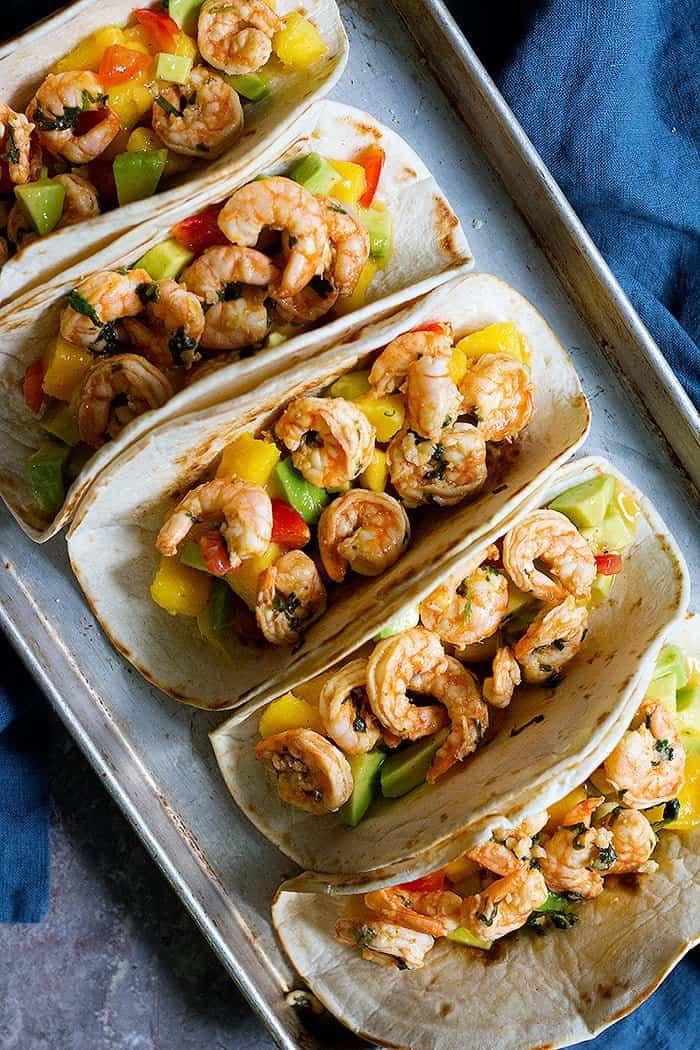Fill taco tortillas with mango salsa and shrimps.