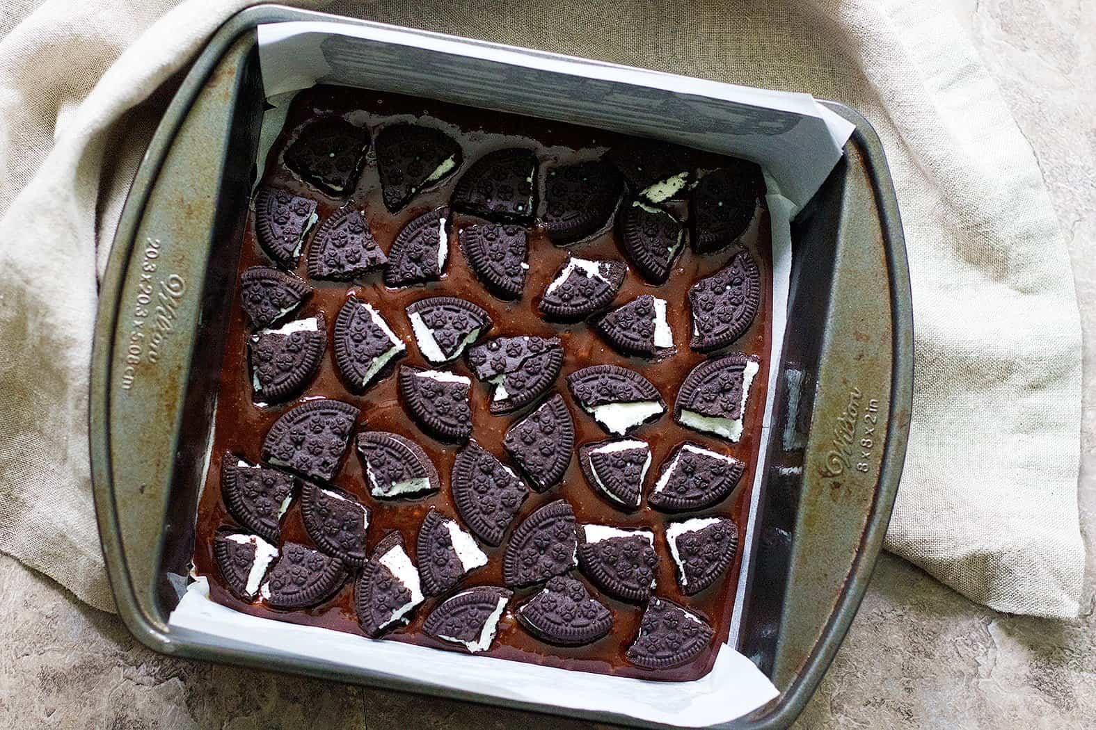 Pour half of the brownie batter into the prepared pan and layer half of the oreo pieces on top.