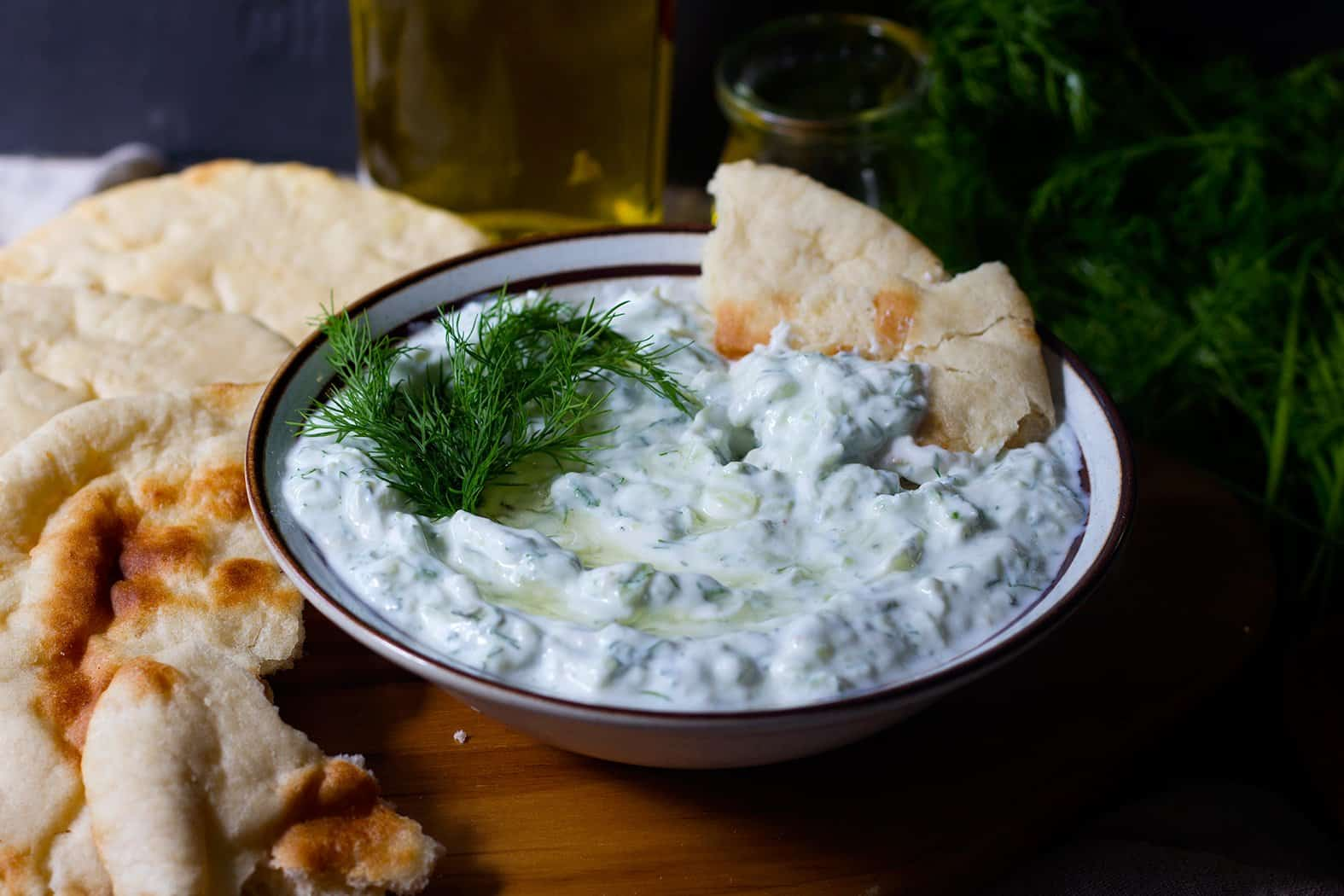 Greek Tzatziki sauce is served in a bowl with pita bread.
