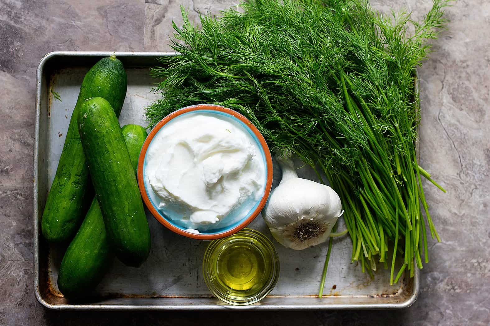 For easy tzatziki sauce you need cucumbers, yogurt, garlic, fresh dill and olive oil.