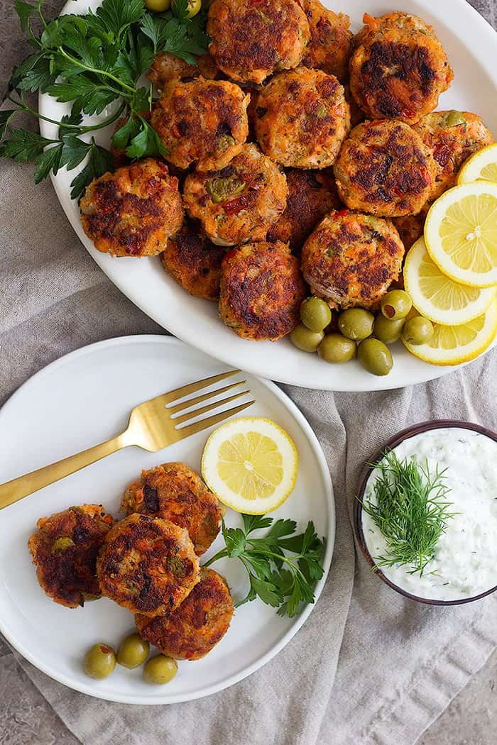 Homemade salmon cakes in a platter with olives, lemon and parsley.