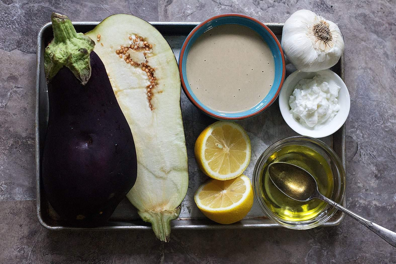 Baba Ganoush ingredients are eggplants, tahini, garlic, yogurt, lemon juice and olive oil.