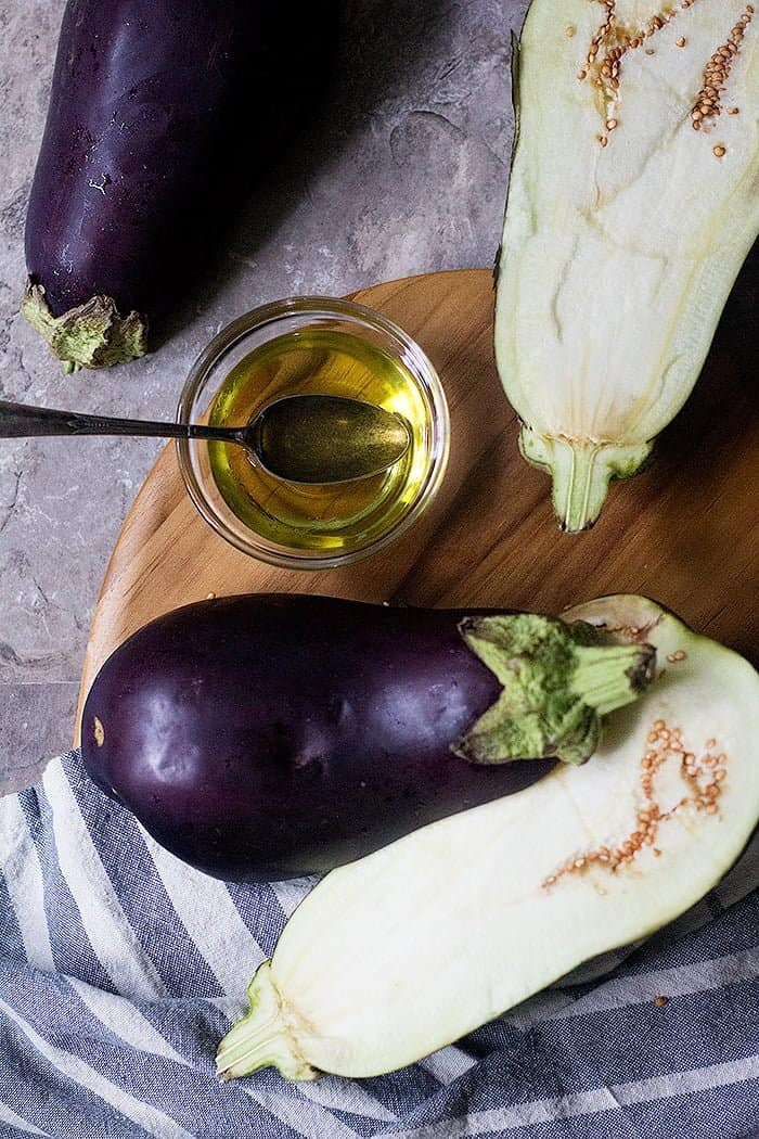 To roast eggplant cut them in half and brush with olive oil.