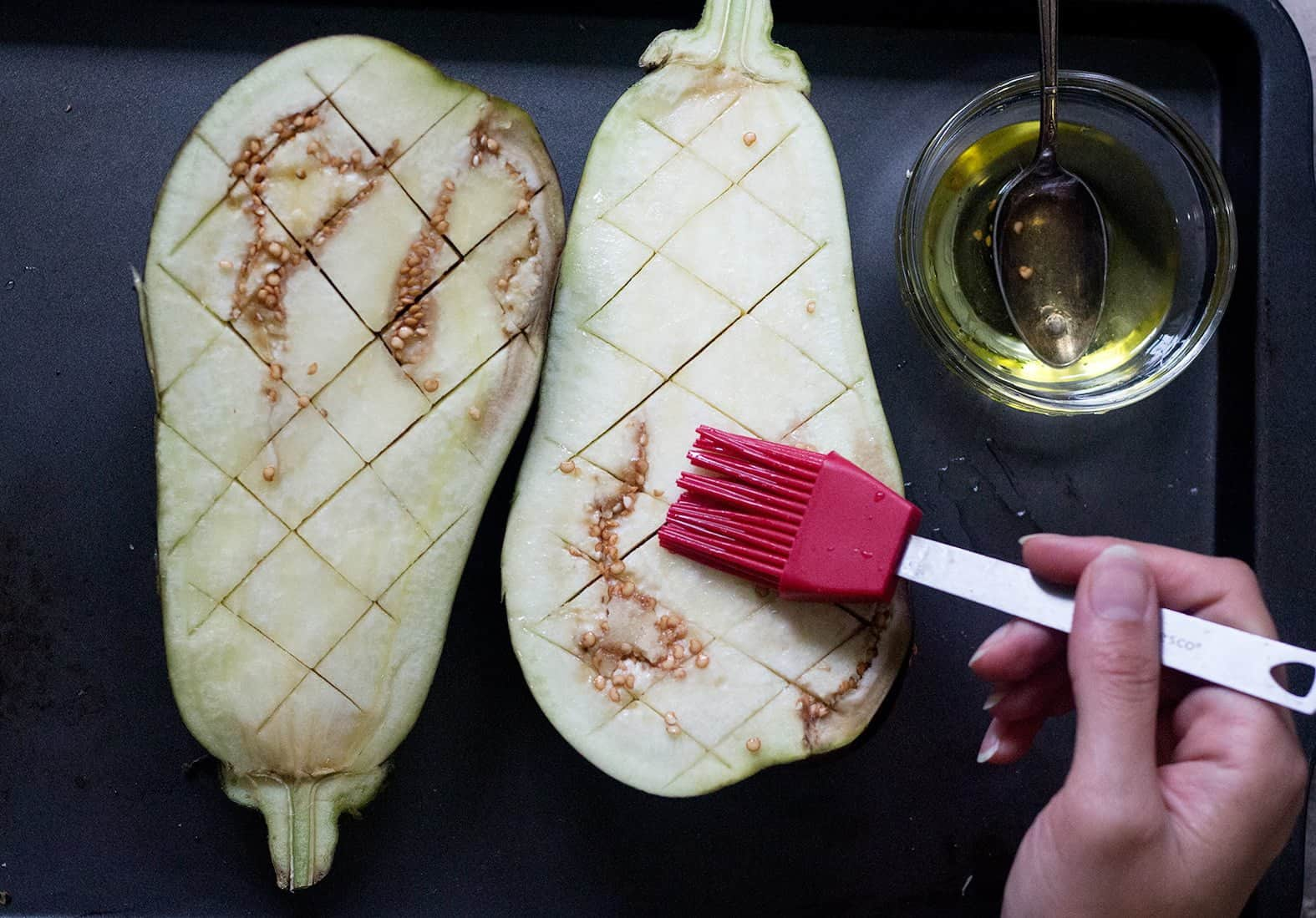 To make roasted eggplant in the oven cut diamonds in the eggplant without cutting the skin. Brush with extra virgin olive oil.