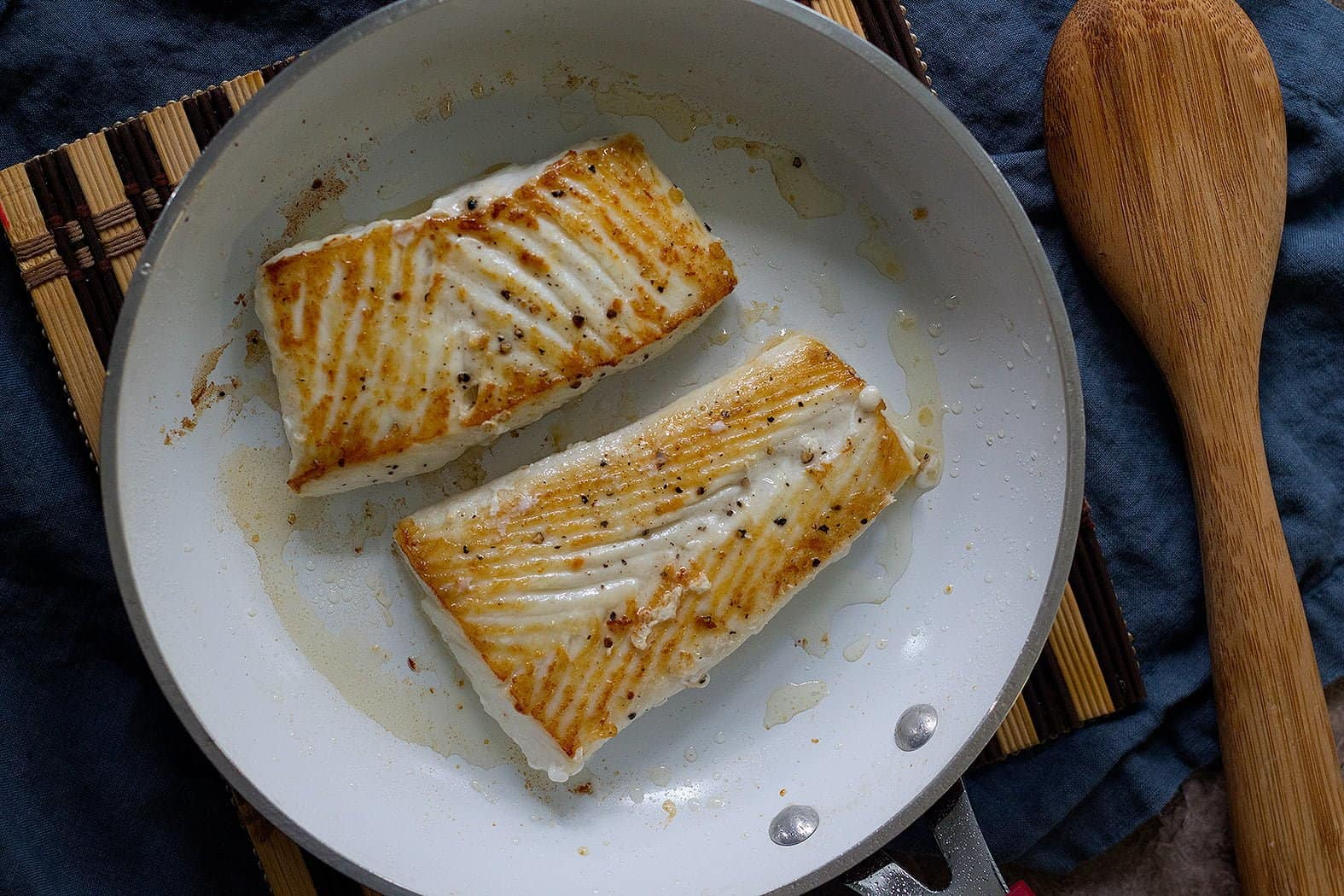place the Alaska halibut fillets in the pan, seasoned side down. Sprinkle more salt and pepper on the top side. Pan-sear undisturbed for four to five minutes until it's golden brown and crispy.