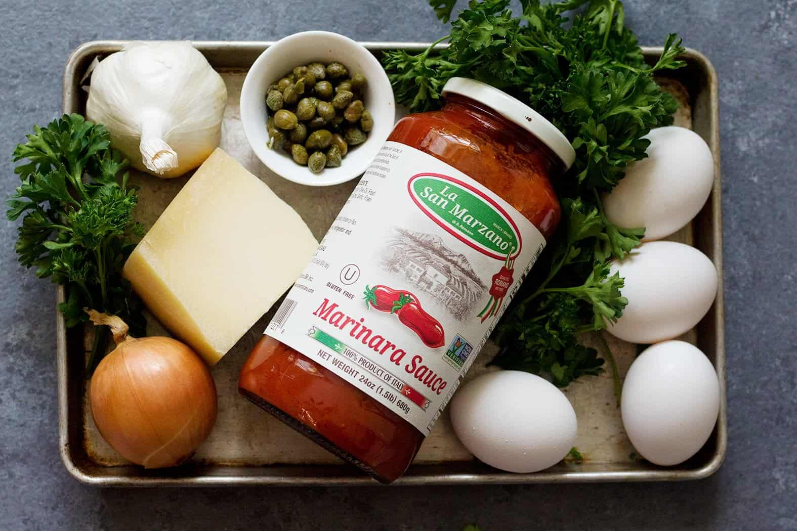 Ingredients to make baked eggs: onions, bell pepper, eggs, La San Marzano Marinara sauce, capers, eggs, parmesan and mozzarella cheese.