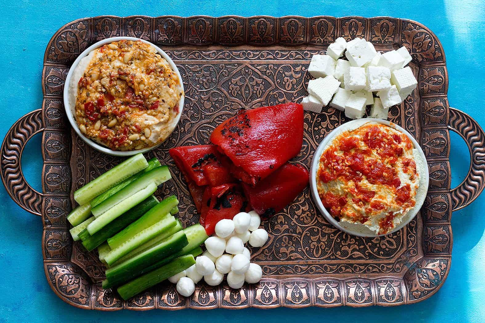 Place hummus, cucumber and cheese on the tray.