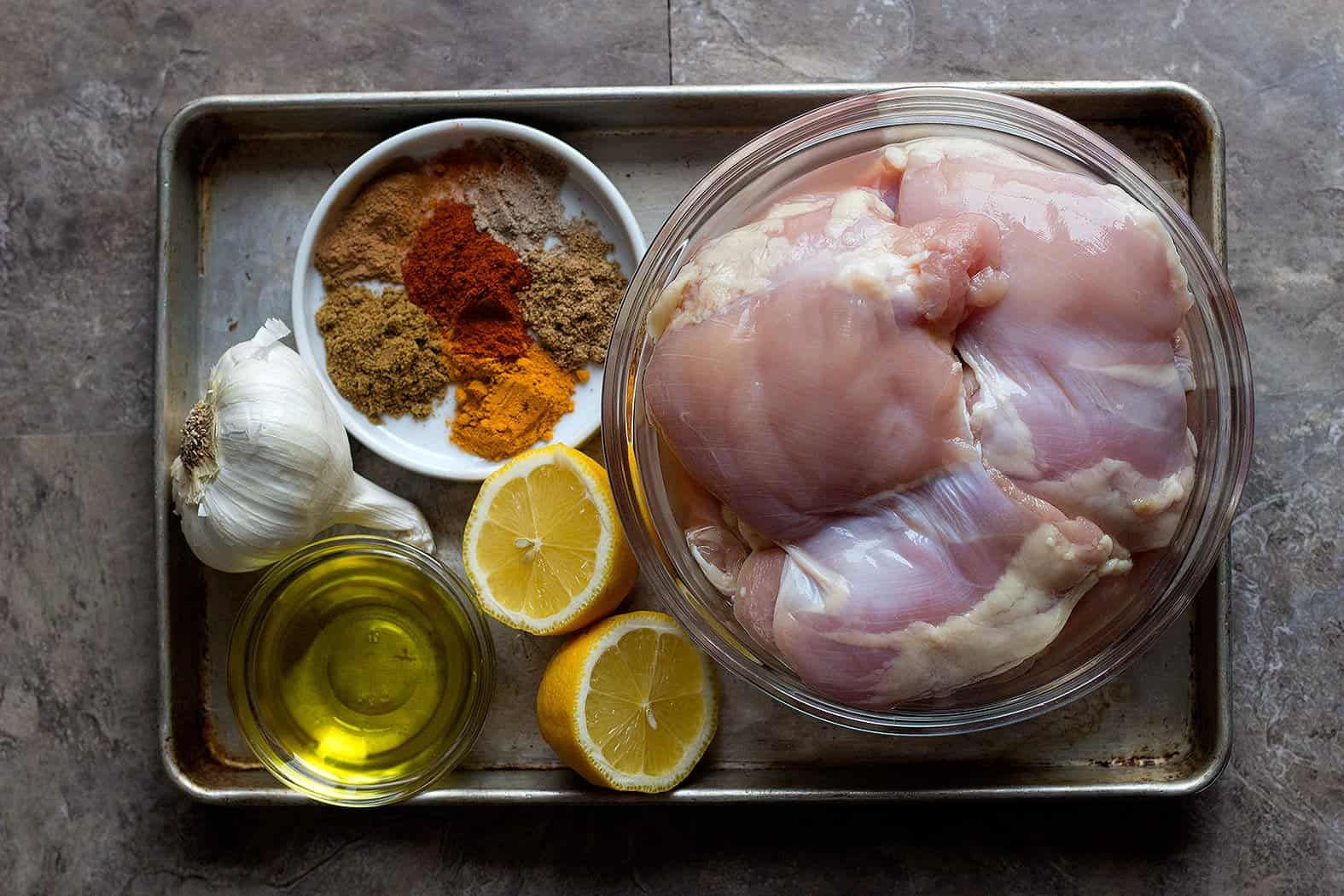 To make this recipe you need chicken thighs, a mix of spices, lemon and garlic.