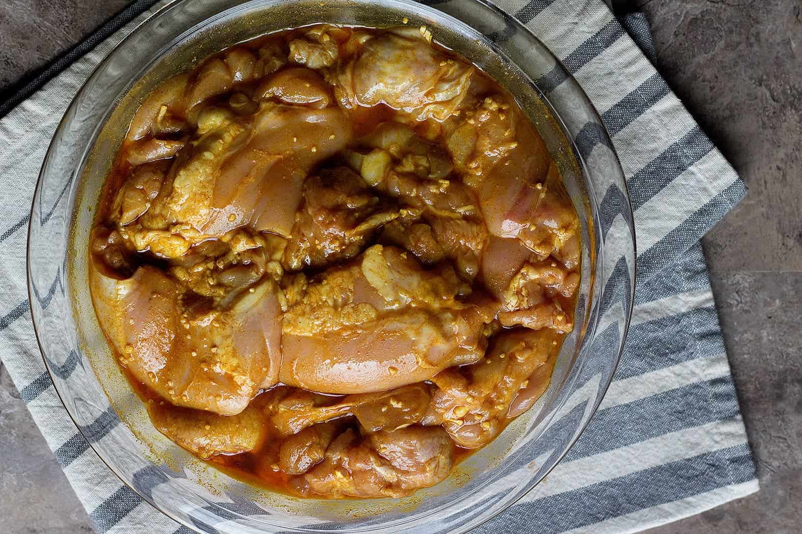 To make the marinade for chicken shawarma, mix all the spices in a large bowl and add in olive oil, lemon juice and garlic.