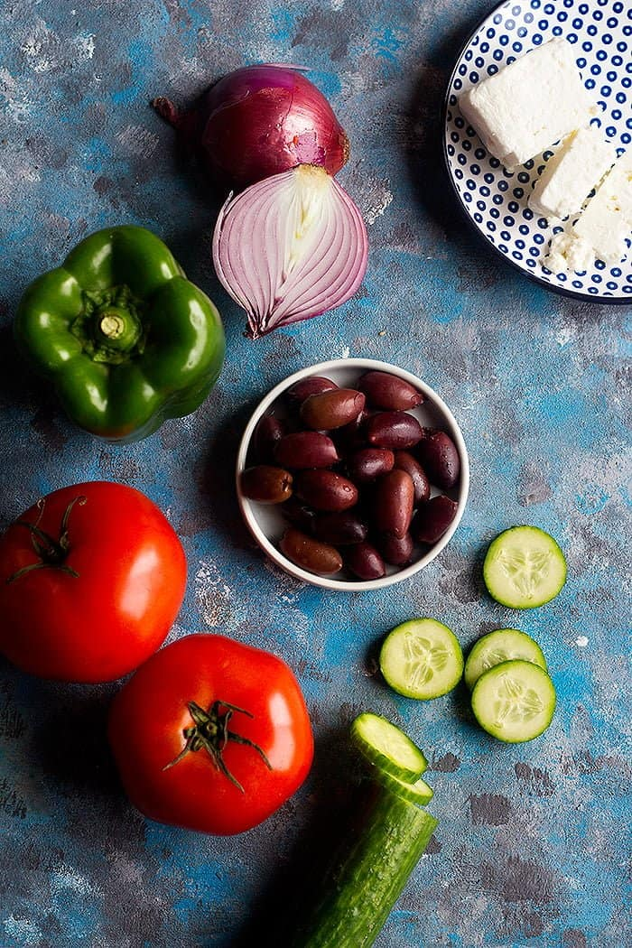 Ingredients to make Mediterranean Greek salad are olives, tomatoes, bell pepper, feta cheese, onion and cucumber.