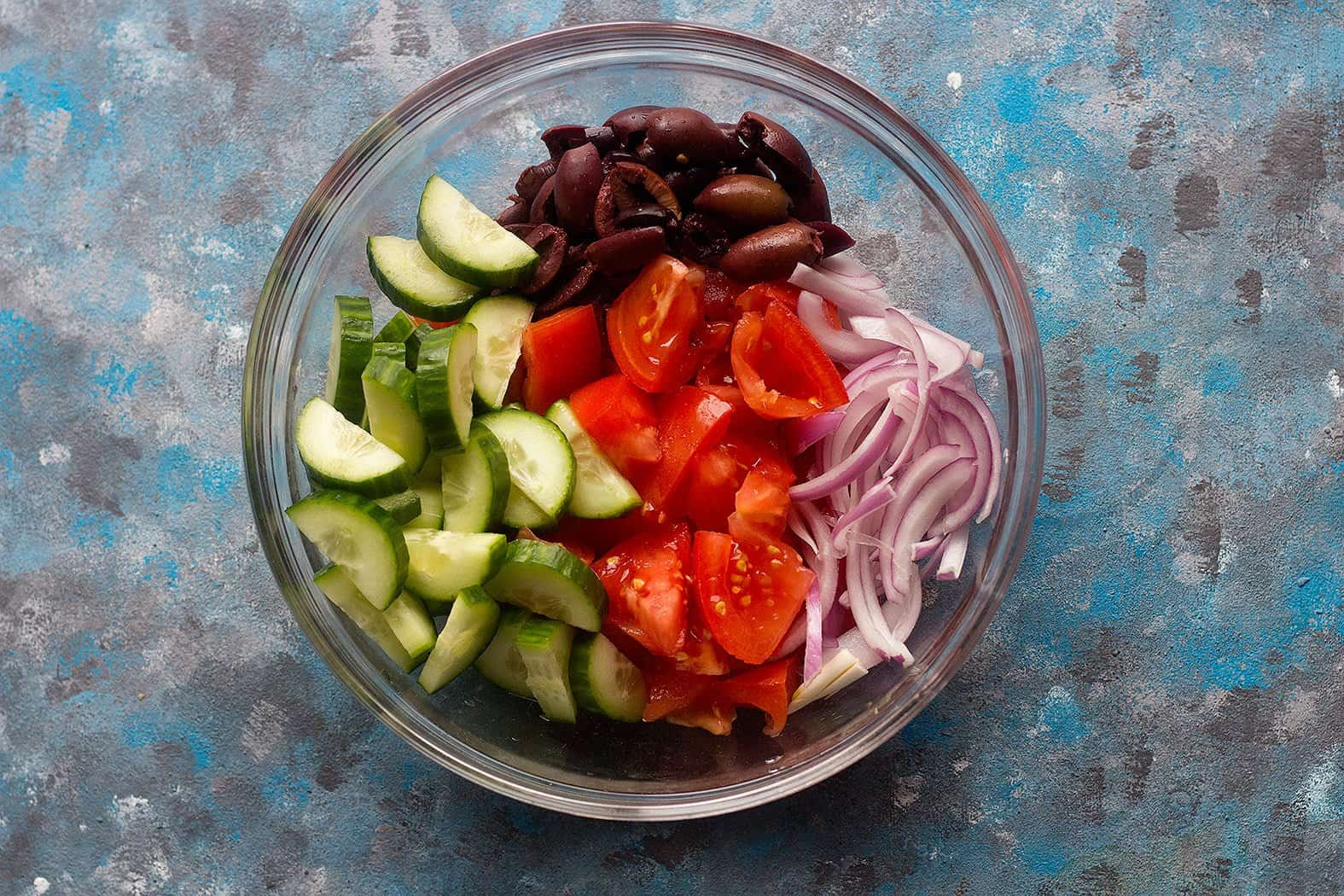 To make authentic Greek salad, chop all the ingredients into large chunks.
