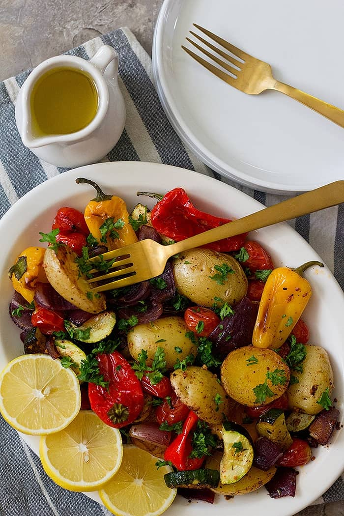 A platter of roasted vegetables with some olive oil.